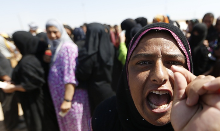 A displaced Iraqi woman queues with others to register at a camp sfor people fleeing violence in northern Iraq on 17 June in Aski kalak, west of the Kurdish autonomous region's capital Arbil. Photograph: Karim Sahib/AFP/Getty Images