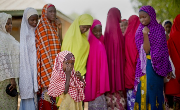 A young Nigerian girl from the Hausa tribe stands next to the line as her mother joins others queuing to validate their voting cards, at a polling station located in an Islamic school in Daura, the home town of opposition candidate Gen. Muhammadu Buhari, in northern Nigeria Saturday, March 28, 2015. Nigerians went to the polls Saturday in presidential elections which analysts say will be the most tightly contested in the history of Africa's richest nation and its largest democracy. (AP Photo/Ben Curtis)
