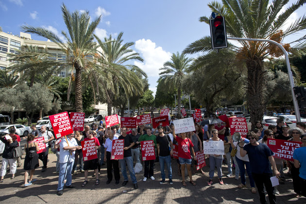 "Left wing activists hold signs during a demonstration in Tel Aviv, Israel, Friday, Oct. 9, 2015. At least four attacks — three by Palestinians and one by an Israeli — threatened to escalate and spread throughout the country as Israeli police struggled to control spiraling violence. Hebrew on signs read: ""you want security, stop the occupation."" and ""Jews and Arabs refuse to be enemies."" (AP Photo/Sebastian Scheiner)"